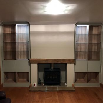 A pair of bespoke cabinets fitted into alcoves of the front room, glass doors for displays