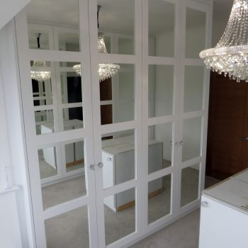 Wardrobes with square edged shaker style doors and mirror to panels