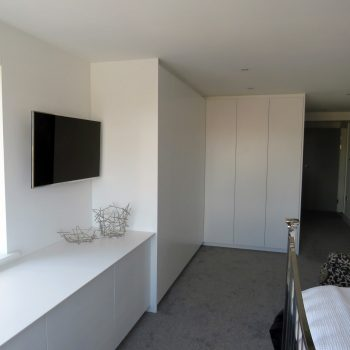 White spray painted wardrobes, doors are a flush design, push to open wardrobe doors