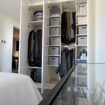 Wardrobe doors open to show shelving and clothes rails