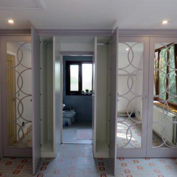 Bespoke wardrobe, Half moon fretwork doors, concealed entrance to bathroom