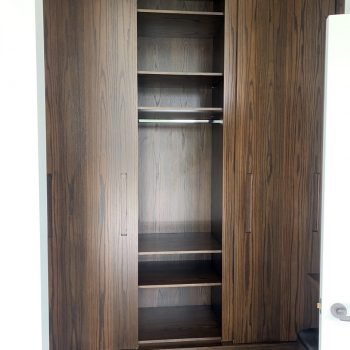 Bespoke Wardrobes with one of the sliding doors open to reveal the carcase behind, Oak Veneered MDF